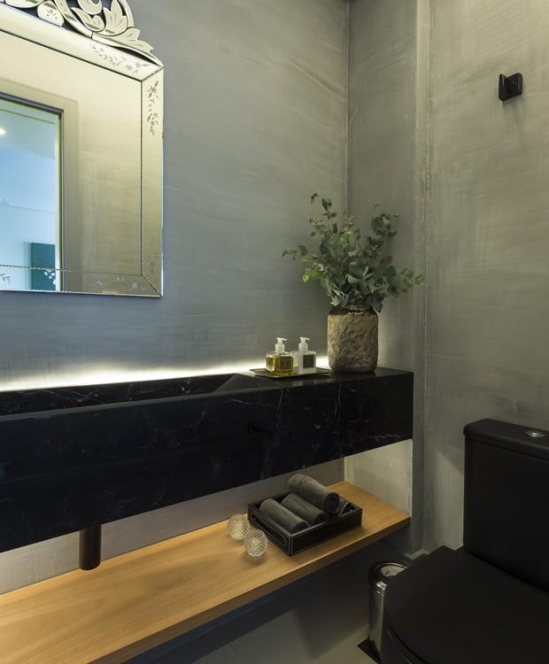 Louças pretas e cimento queimado conferem o tom moderno ao lavabo. O espelho veneziano, no entanto, traz mais uma vez o clima clássico para perto  (Foto: Mariana Boro/Divulgação)