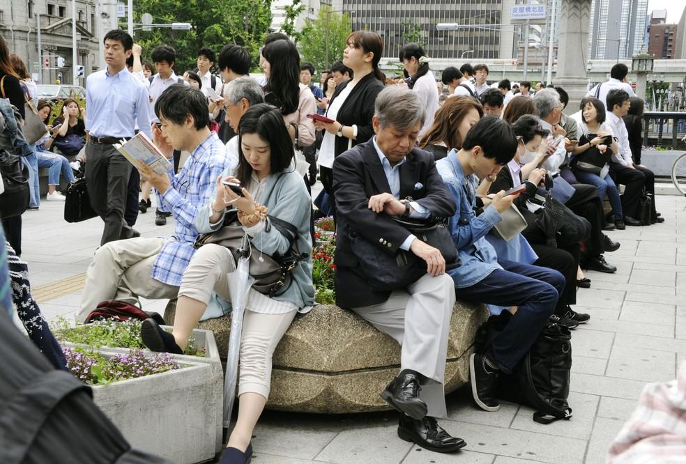 Trabalhadores esperam liberação de estação de trem em Osaka após terremoto (Foto: Kyodo/via Reuters)