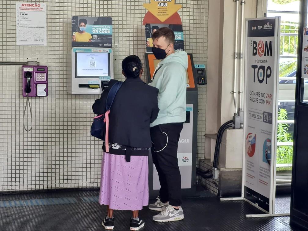 Funcionário de empresa responsável pela implementação de QR Codes nos bilhetes auxilia senhora na compra de passagem — Foto: Bárbara Muniz Vieira