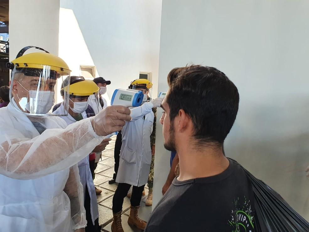 Autoridades de saúde testam temperatura de quem entra no Paraguai pela Ponte da Amizade — Foto: Renan Gouvêa/RPC Foz do Iguaçu