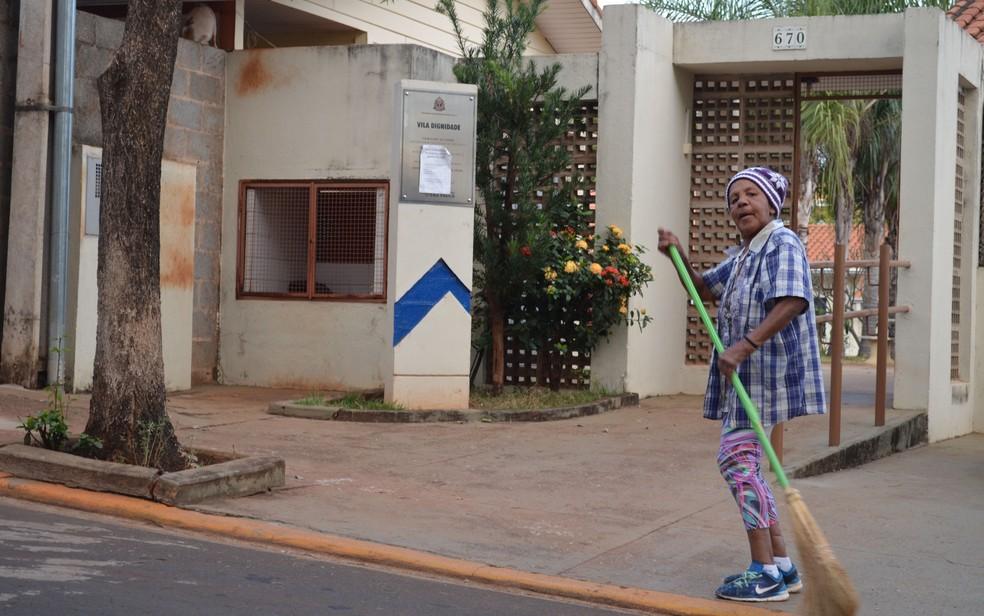 A aposentada Márcia Gouveia, de 69 anos, varrendo em frente a Vila Dignidade — Foto: Werlon Cesar/G1