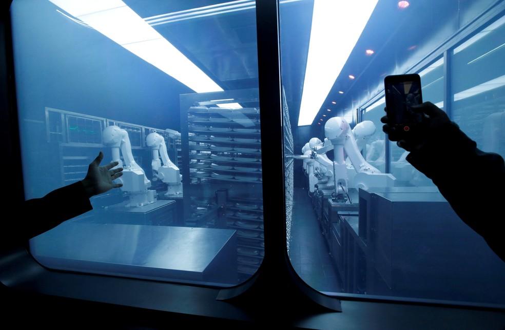 Clientes tiram fotos enquanto braços robóticos coletam pratos pré-embalados de acordo com os pedidos de jantar no novo restaurante de inteligência artificial Haidilao em Pequim, na China — Foto: Jason Lee/Reuters