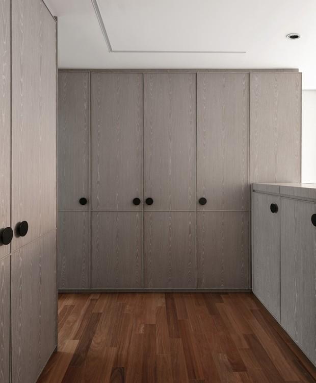 Closet | Por estar na entrada do quarto, os armários ganharam uma folha especial com tingimento cinza, resultando no aspecto neutro de painel. A bancada serve de cabeceira para a cama ali encostada do outro lado. (Foto: Alessandro Gruetzmacher/Divulgação)