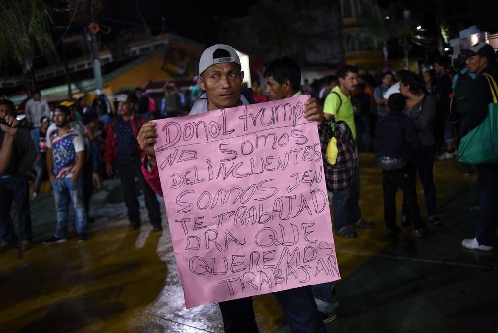 Migrante hondurenho exibe cartaz com a mensagem 'Donald Trump, não somos criminosos, somos trabalhadores que querem trabalhar'  — Foto: Johan Ordonez / AFP