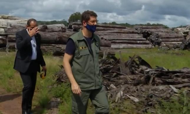 Ricardo Salles caminha diante das dezenas de milhares de toras de madeira apreendidas no Pará; ministro do Meio Ambiente defende legalidade da extração das árvores, mas PF aponta origem em terras griladas