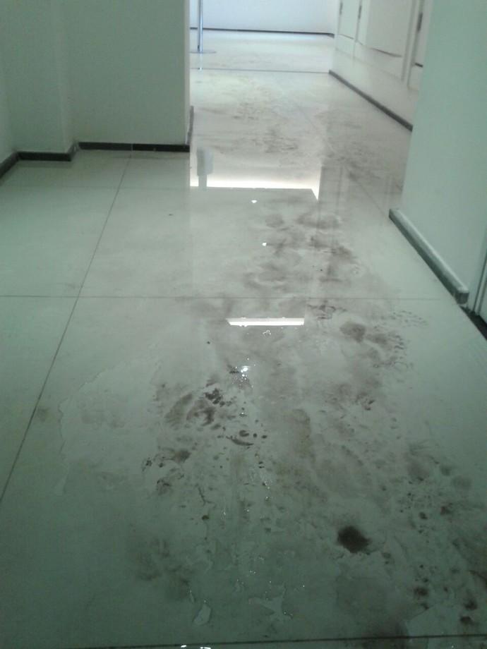 Reflexo da água que tomou o chão do acesso à escada de emergência, atrás da recepção, no prédio 23 (Foto: GloboEsporte.com)