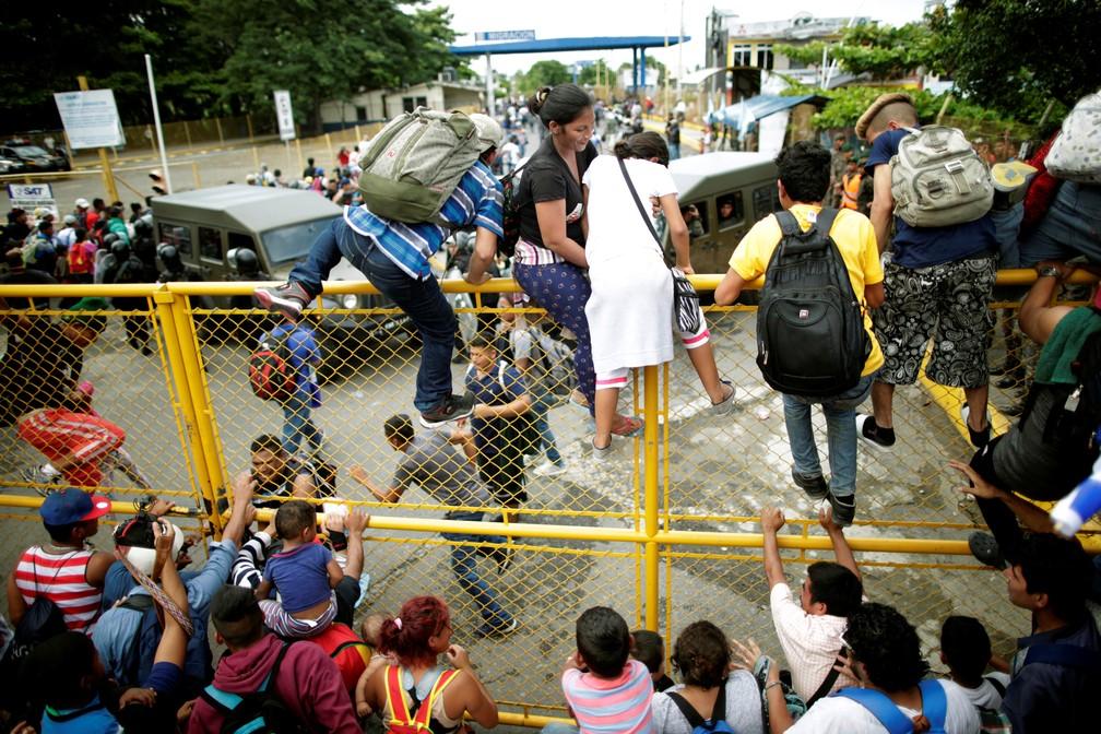 Imigrantes pulam grade na fronteira da Guatemala com o México nesta sexta-feira (19); caravana com milhares de imigrantes atravessa rumo aos EUA — Foto: Ueslei Marcelino/Reuters