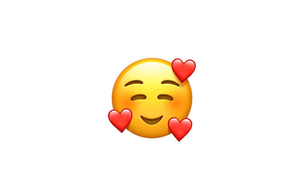 Mais uma opção para os apaixonados, a carinha sorridente com três corações está entre os destaques do iOS 12.1 — Foto: Reprodução/Emojipedia