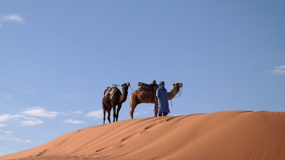 Camelos e homem em trajes típicos contra o deserto sobre duna no Saara marroquino (Foto: TV Globo/Reprodução)