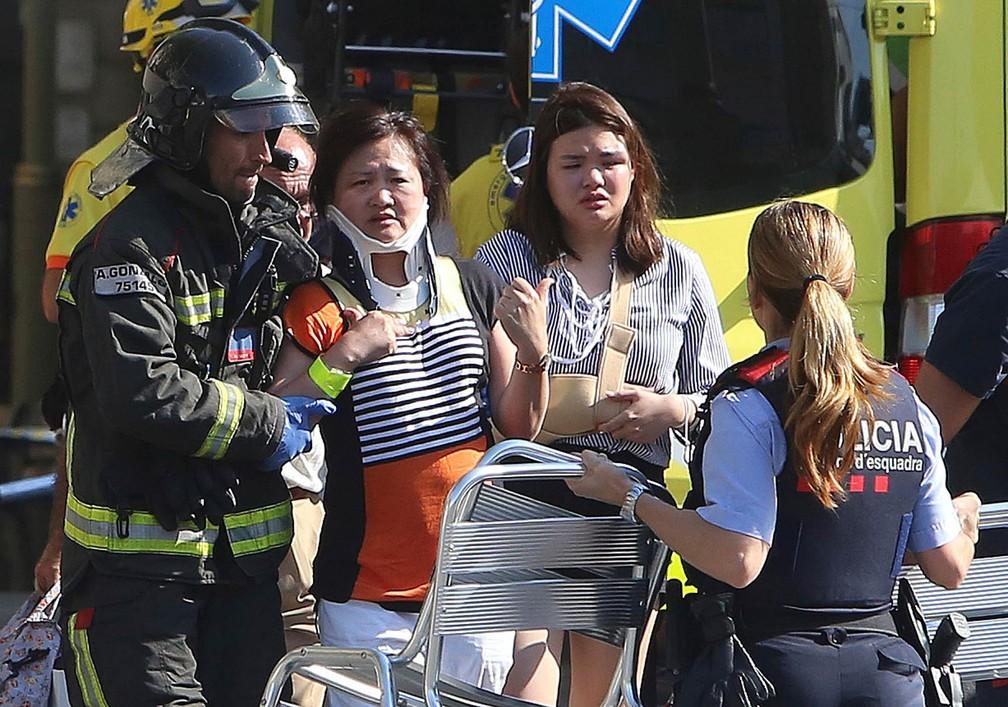 Mulheres feridas recebem tratamento após atentado com uma van que foi usada para atropelar diversas pessoas nas Ramblas de Barcelona (Foto: Oriol Duran/AP)