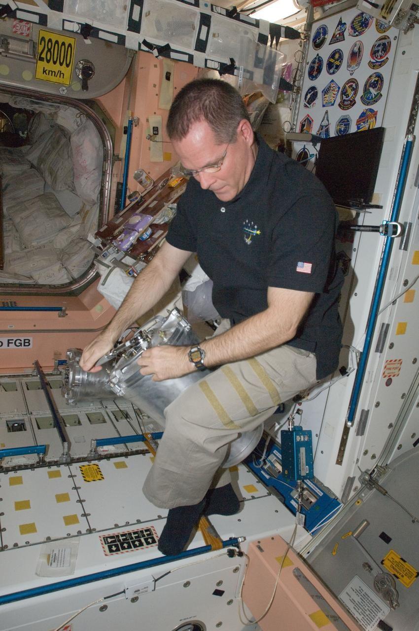 Astronauta da NASA, Kevin Ford, faz rotina de manutenção do compartimento de descarte e higiene na ISS (Foto: NASA)
