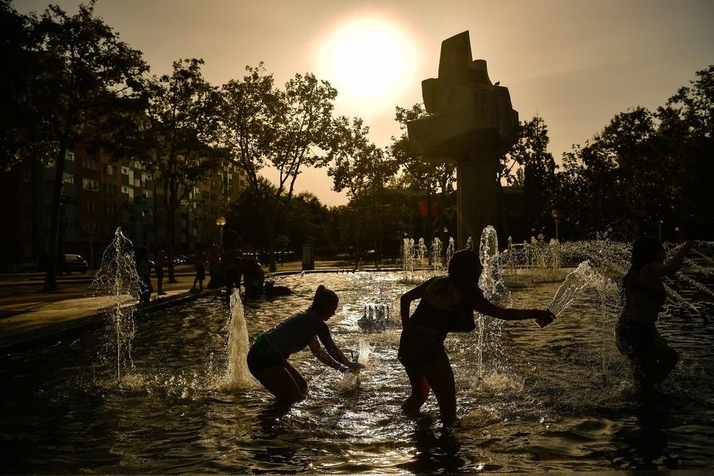 Pessoas se divertem em fonte em dia de calor intenso na cidade basca de Vitória, no norte da Espanha  — Foto: Alvaro Barrientos/AP