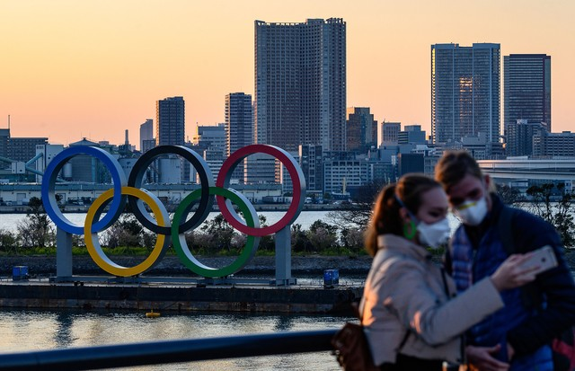People wear face masks as they take pictures in front of the Olympic Rings at the Odaiba Seaside Park in Tokyo on March 6, 2020. - Construction of all new permanent venues for the Tokyo 2020 Olympics and Paralympics is now complete, organisers said on Mar (Foto: AFP via Getty Images)