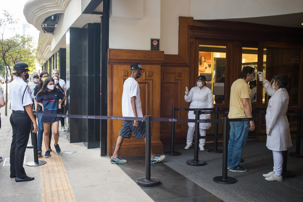 Consumidores tem a temperatura aferida antes de entrarem no Shopping Pátio Paulista, na Bela Vista, na região centro-sul da cidade de São Paulo, por volta das 16h desta quinta- feira, 11 de junho de 2020 — Foto: TIAGO QUEIROZ/ESTADÃO CONTEÚDO