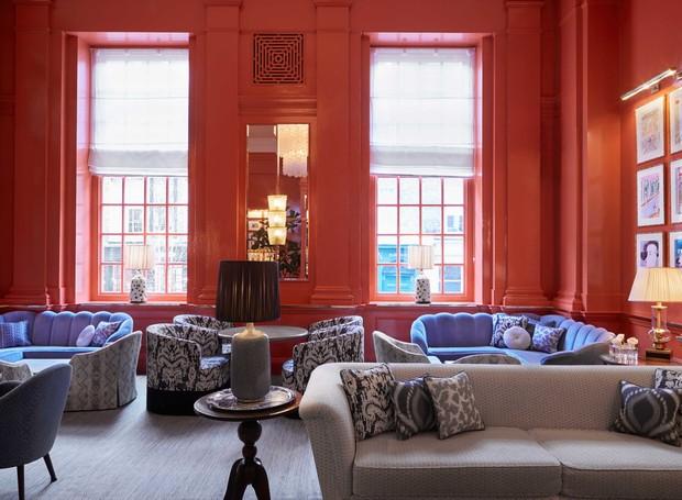 Na decoração do The Coral Room, a cor do ano ilustra as paredes e não há espaço para o excesso: poltronas estampadas e acabamentos dourados completam a estética maximalista (Foto: The Coral Room/ Reprodução)