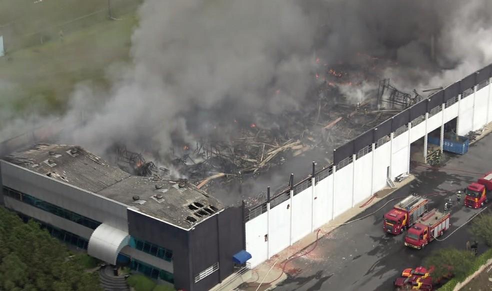 Mesmo após 15 horas, bombeiros ainda tentam controlar fogo em barracão de Curitiba — Foto: Reprodução/RPC