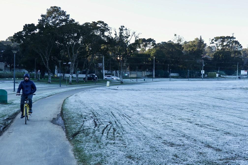 Ciclista encarou o frio e pedalou no Parque Barigui, que estava coberto pela geada — Foto: Ricardo Marajó/FAS
