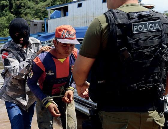 Homem mascarado entrega à polícia um acusado de matar mãe e filho. Henrique, o suspeito, quase foi linchado — e nada teve a ver com o crime (Foto: Adriano Machado/Época)