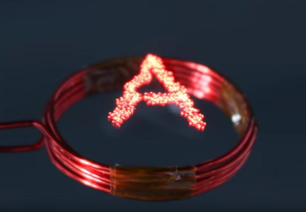 Lucíola é o nome dado à luz eletrônica desenvolvida no Japão. Partícula emite um brilho vermelho que pode iluminar um texto (Foto: Reprodução/YouTube/ERATO Kawahara UIN Project)