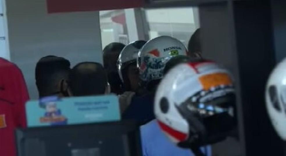 Presidente Jair Bolsonaro (de camisa azul e capacete branco) sem máscara em loja de moto no DF — Foto: Reprodução/TV Globo
