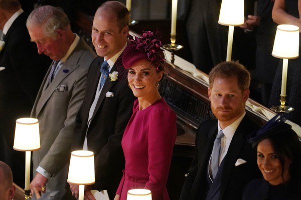 A atriz Meghan Markle com o príncipe Harry e ao lado do príncipe William e de Kate Middleton durante o casamento da prima dos dois príncipes, princesa Eugenie (Foto: Getty Images)