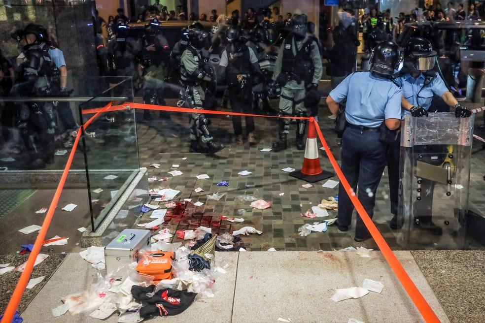Área com sangue e detritos é isolada pela polícia na entrada de um shopping após um ataque com faca que feriu seis pessoas em Hong Kong — Foto: Vivek Prakash/AFP