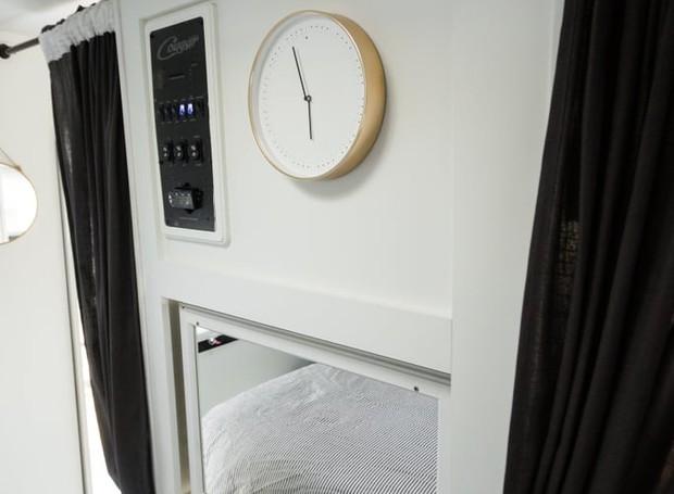 No quarto do casal, um espelho cobre o espaço aberto, que quarta uma televisão no cômodo ao lado. Ao remover o objeto, o casal pode assistir tv da cama (Foto: Brianne and Sean Walker/ Reprodução)