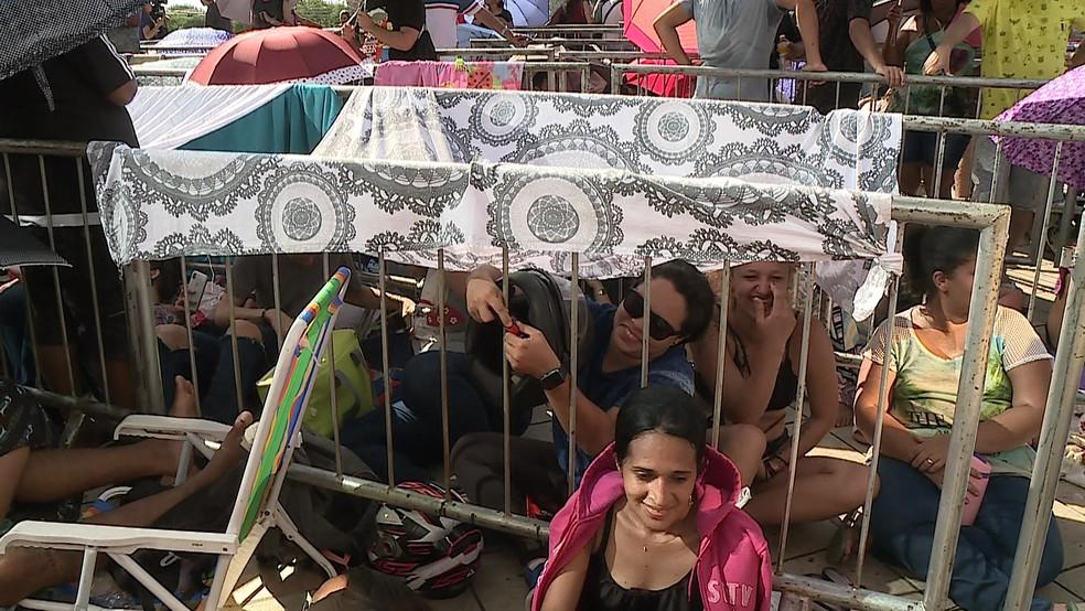 Fãs de Sandy e Junior levaram panos e sombrinhas para se proteger do sol enquanto esperam na fila â?? Foto: Reprodução/TV Globo