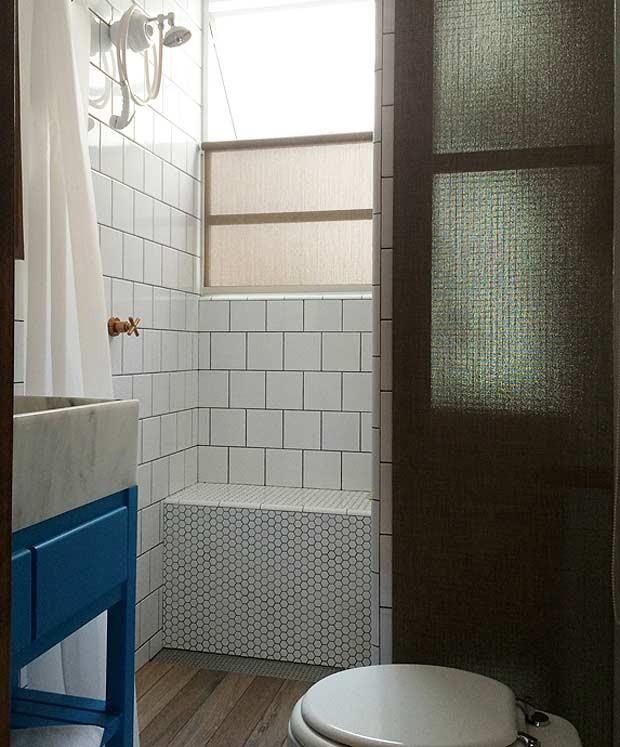 Bem iluminado, o banheiro da suíte ganhou inspiração nos vestiários. A janelas são da Serralheria Ideal. O banco no box foi revestido com pastilha sextavada branca 2,5 x 2,5cm. Os pisos e revestimentos são da Revestimenta e Ceramik (Foto: Divulgação/André de Freitas)