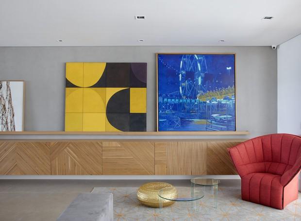 A tela azul de Newton Mesquita pautou a paleta do apartamento. Ela fica no living, apoiada numa longa canaleta que acompanha o bufê desenhado pela arquiteta e apoia as principais obras de arte do endereço (Foto: Denilson Machado/MCA Estúdio/Divulgação)
