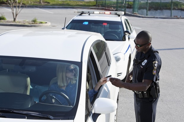 Woman (30s) driving car, pulled over by African American police officer (20s). (Foto: Getty Images)