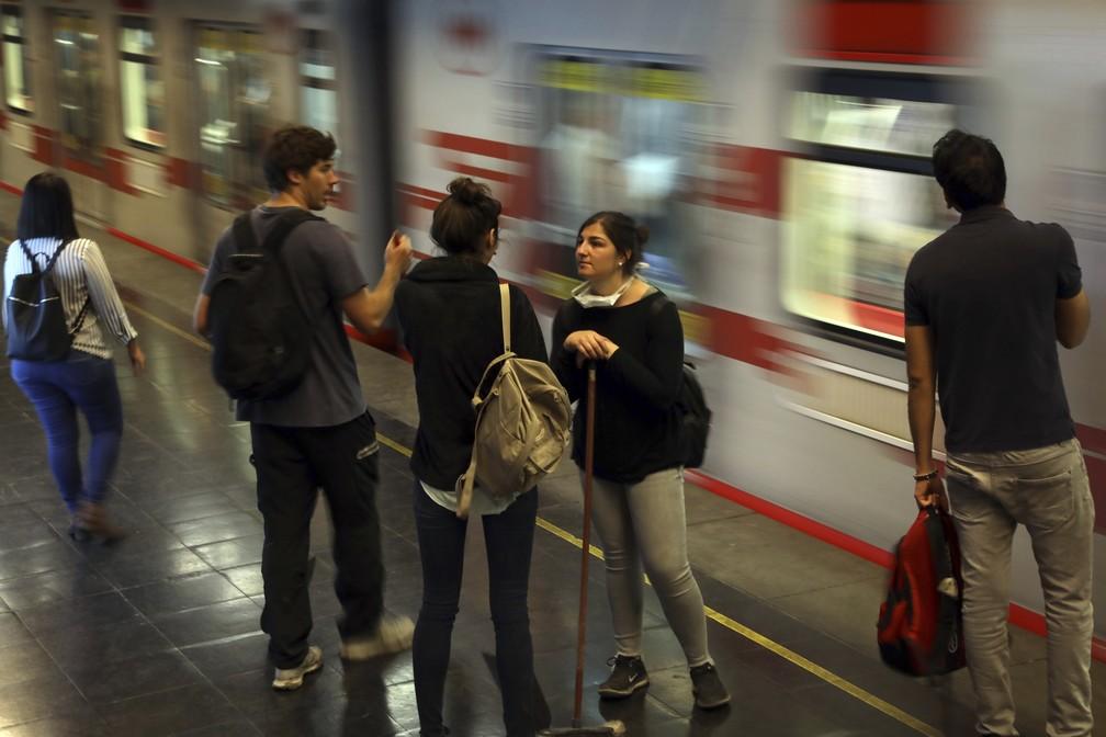 Estudantes aguardam metrô, cujo serviço voltou a funcionar parcialmente em Santiago, no Chile, nesta quinta-feira (24) — Foto: Rodrigo Abd/AP Photo