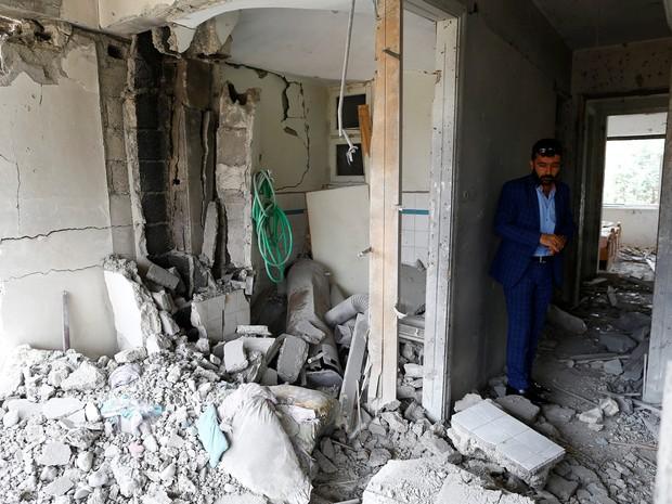 Omer Ciloglu observa sua casa destruída após ser atingida por um foguete disparado da Síria (Foto: Osman Orsal/Reuters)