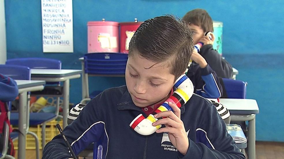 'Sussurrofone' auxilia os estudantes a ouvirem melhor a pronúncia das palavras e, assim, melhorar o desempenho na escrita, segundo professores (Foto: Reprodução/RPC)