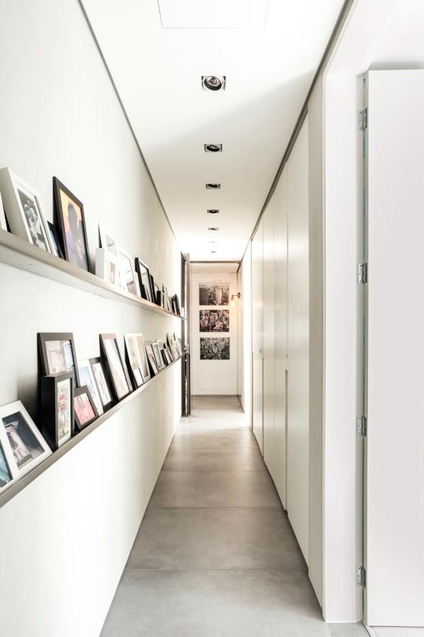 Canaletas de aço inox na parede apoiam fotos de família sem atrapalhar a circulação no corredor projetado pelo arquiteto José Ricardo Basiches (Foto: Ricardo Bassetti / Divulgação)