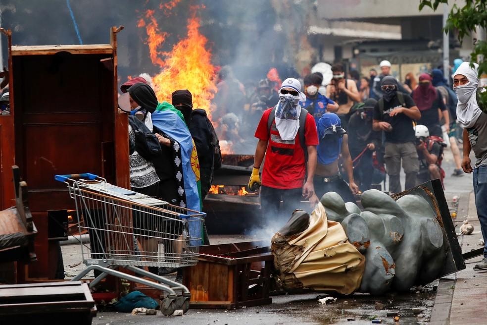 Manifestantes mascarados montam barricada com objetos de igreja de Santiago, no Chile — Foto: Jorge Silva/Reuters