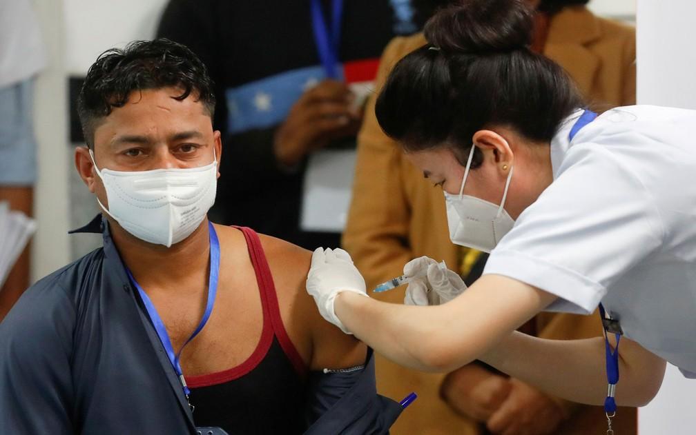 Manish Kumar, que segundo as autoridades indianas, foi a primeira pessoa no país a ser vacinada contra a Covid-19 no país — Foto: Adnan Abidi/Reuters