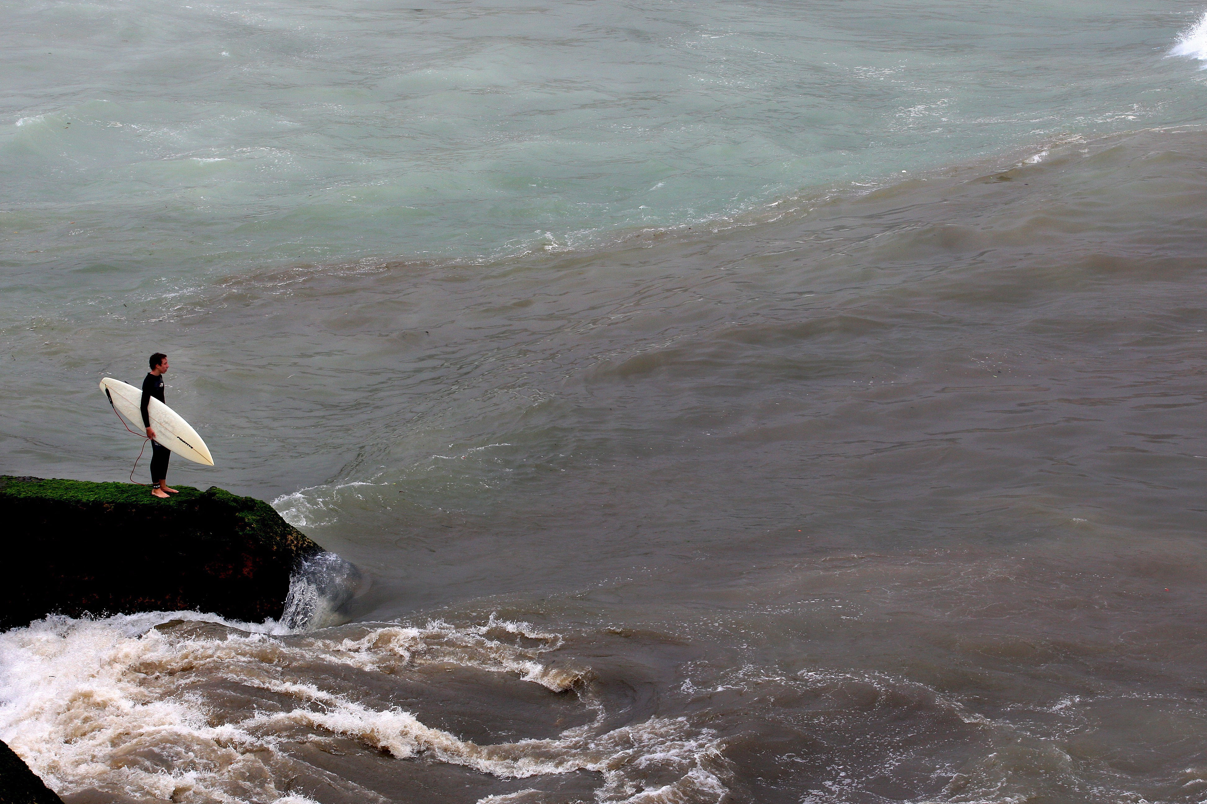Surfista se prepara para pular no mar sujo de esgoto do Leblon, em 2009