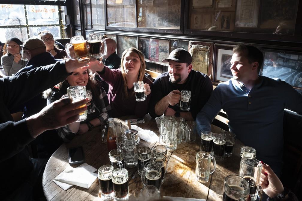Em foto de 27 de dezembro de 2019, clientes levantam suas canecas de cerveja no McSorley's Old Ale House, em Nova York. O bar, aberto na metade do século 19, funcionou ilegalmente durante a Proibição, e continua em funcionamento — Foto: AP Photo/Mark Lennihan