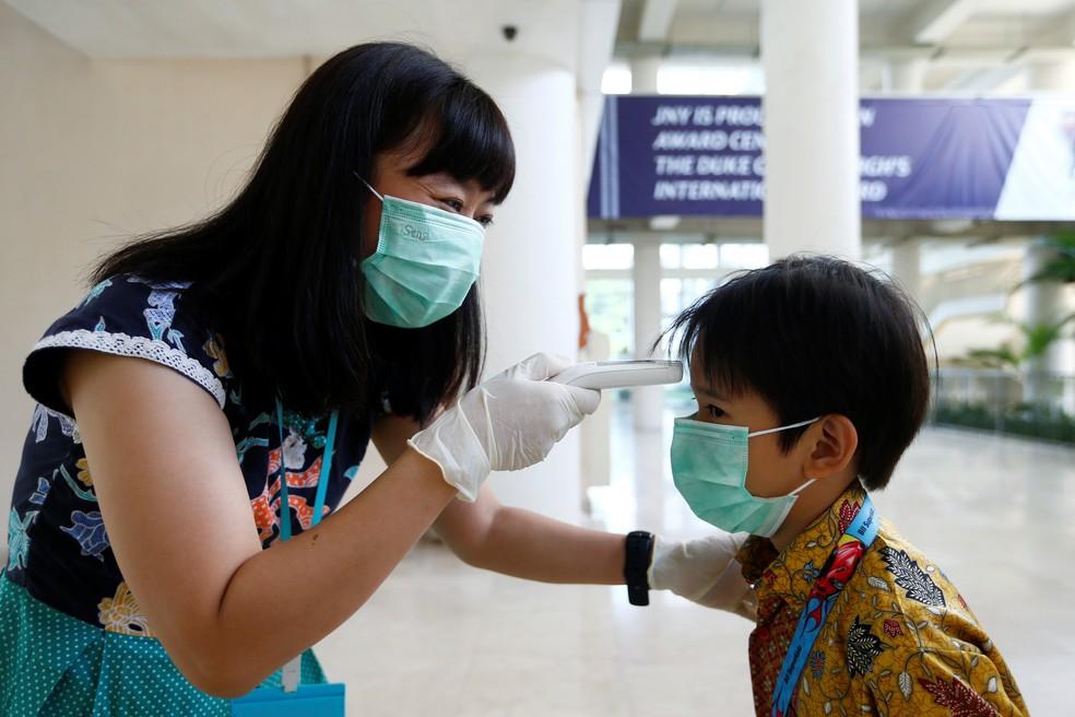 6 de março: Professora checa temperatura de estudante na Indonésia após país confirmar primeiro caso de coronavírus. — Foto: Ajeng Dinar Ulfiana/Reuters