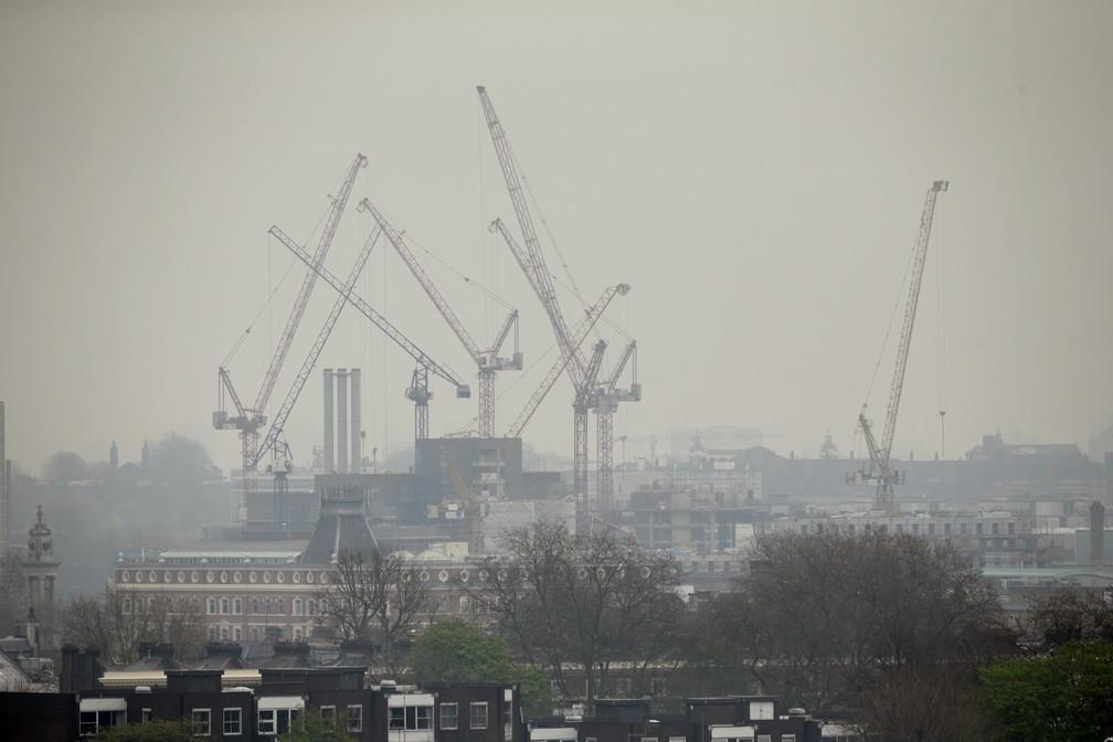 Foto mostra guindastes suspensos em meio à poluição em Londres (Foto: AP Photo/Matt Dunham, file)