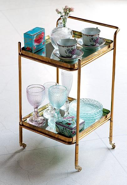 Xícaras, vasos, taças e vasinho com flores decoram este carrinho de chá de ferro, que fica lindo em vários cantos da casa