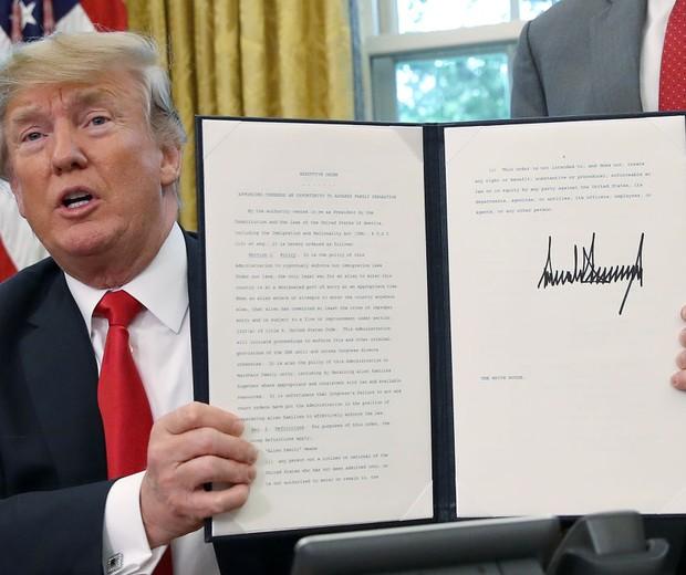 Donald Trump exibe à imprensa o decreto presidencial assinado na quarta-feira (20) (Foto: Getty Images)