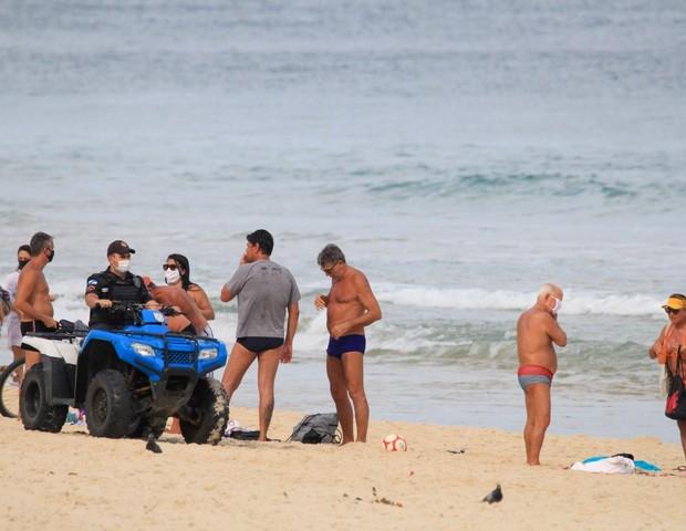 Renata Gaúcho e amigos são advertidos pela polícia na praia de Ipanema (Foto: AgNews)