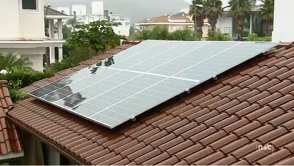 Placas de energia solar instaladas em telhado de casa em SC — Foto: Reprodução/NSC TV