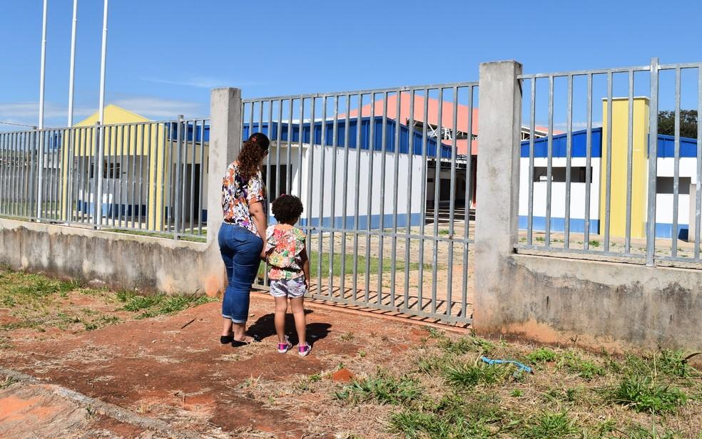 Mãe e filha olham com descrença para CMEI no Buena Vista III, em Goiânia (Foto: Sílvio Túlio/G1)