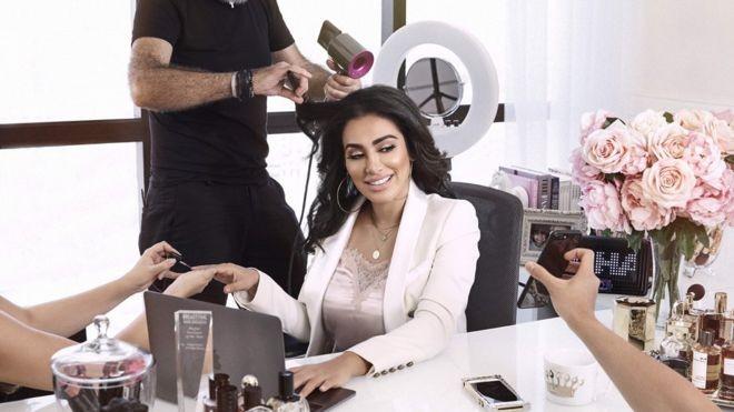 Há 10 anos, Huda Kattan abandonou a carreira de executiva para lançar sua própria marca de produtos de beleza (Foto: HUDA BEAUTY via BBC News Brasil)