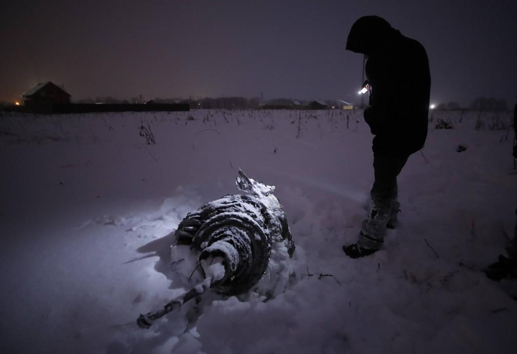 Homem ao lado de um dos destroços do avião da companhia Saratov que caiu perto de Moscou  (Foto: Maxim Shemetov/Reuters)