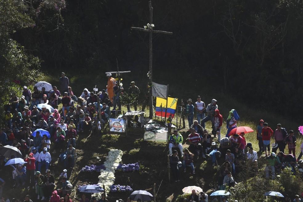 Dezenas de pessoas participaram de missa nesta terça-feira (28) no monte onde restou a fuselagem do avião, na Colômbia (Foto: Joaquin Sarmiento/AFP)