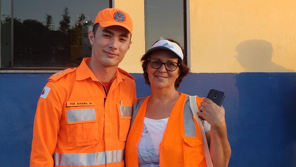O tenente e porta-voz dos bombeiros, Pedro Aihara, posa para fotos com a voluntária Sther Moreira — Foto: Raquel Freitas/G1